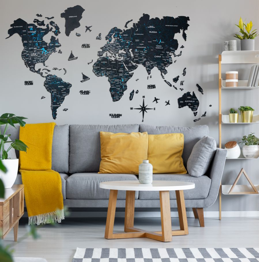 Orange pillows and blanket on grey couch in living room interior with wooden table. Real photo